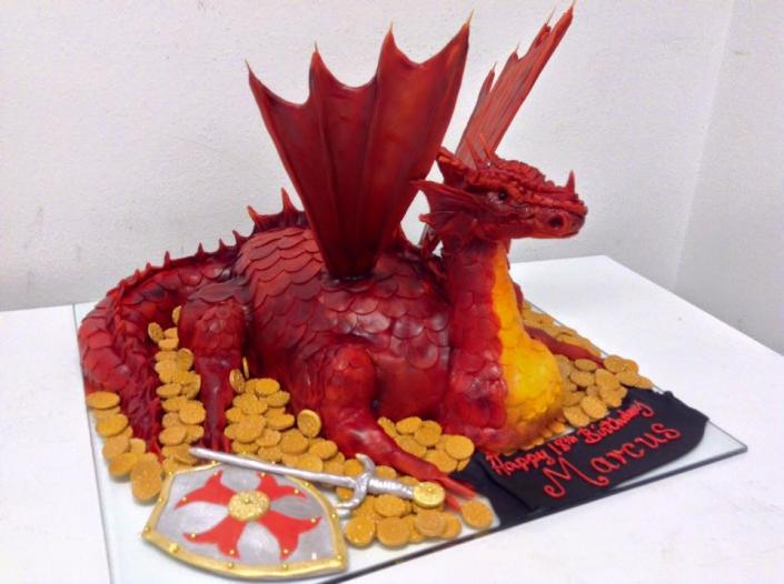 This amazing dragon cake with red and gold frosting will wow your guests!