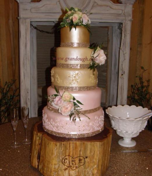 [Image: If you love classic chic style, then this is the cake for you. With soft pink and gold frosting, this will be the highlight for any wedding reception. ]